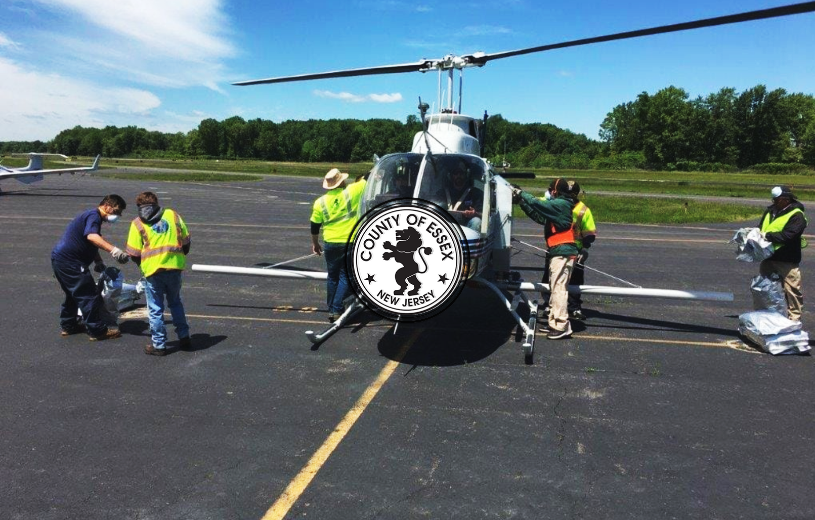 Helicopter with DPW employees preparing to spray aerial larvicides