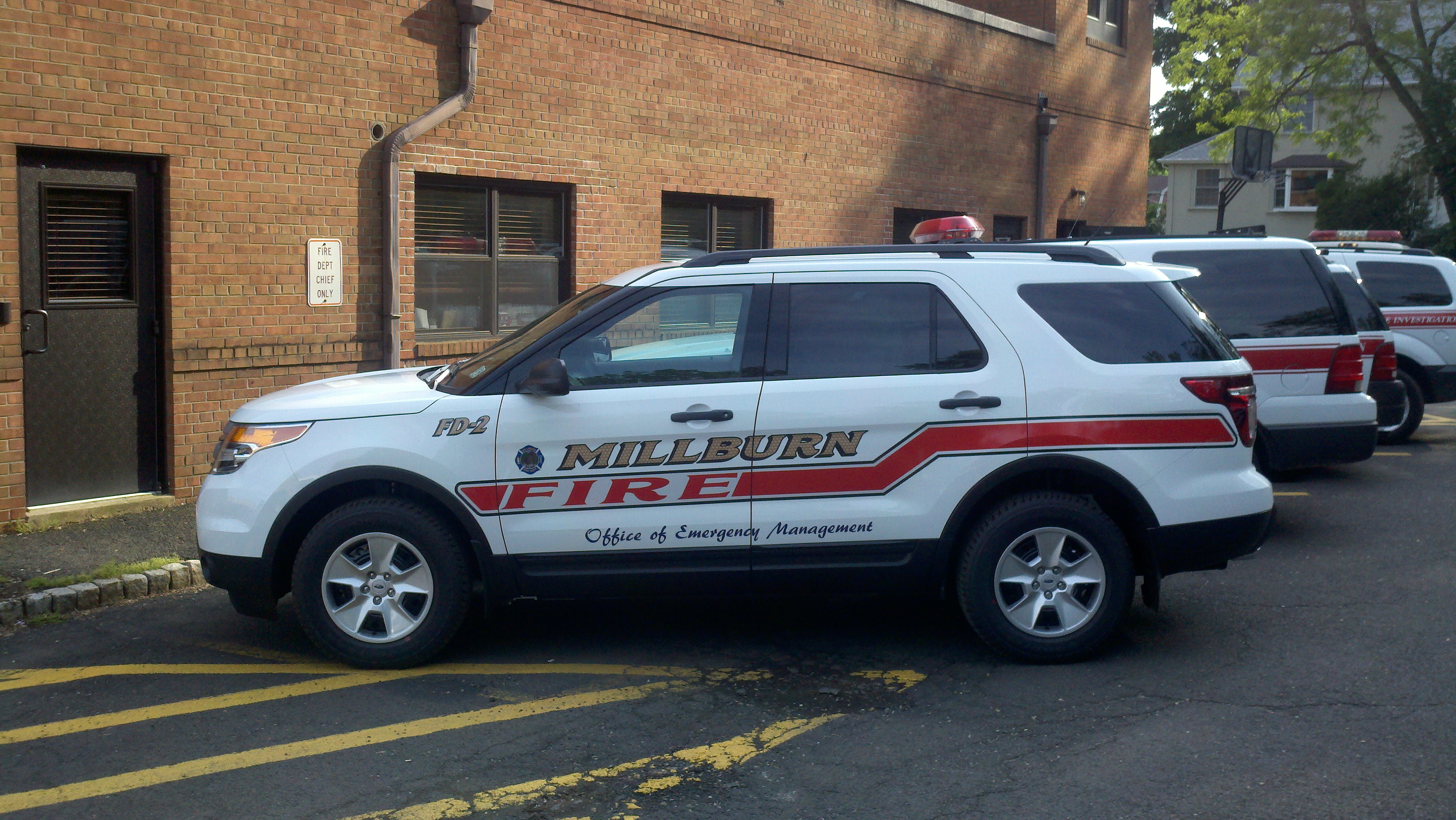 A fleet of white cars with Millburn Fire on the side