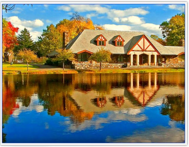 A beautiful house during the fall with its image reflected in the water