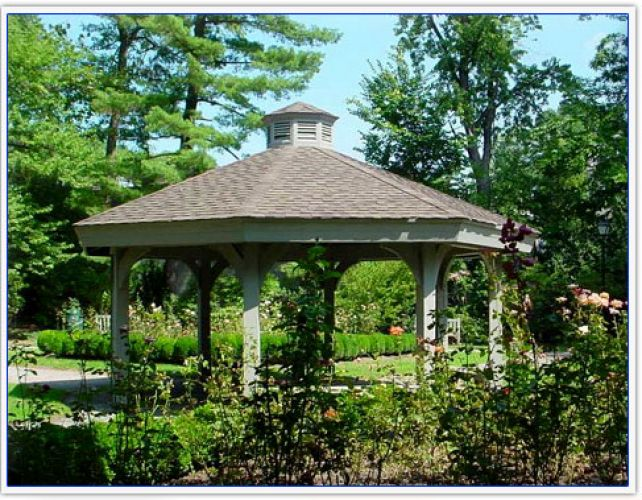 A gazebo in the middle of a green garden