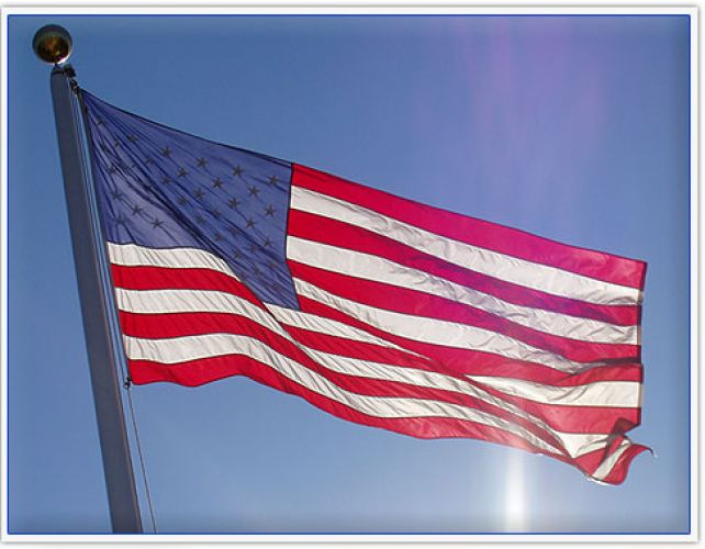 A large American flag backlit by the sun